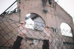 Refugee hands keeping metal fence mesh Kuvituskuvat