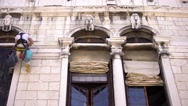 Worker repairing an ancient building in Venice on the wall with a harness. Stock Footage