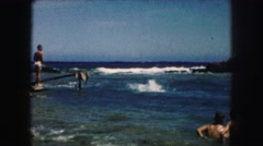 1958: people playing and swimming in the surf along the coast AMES, IOWA Stock Footage