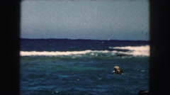 1958: adult and children floating and swimming in blue ocean near waves  Stock Footage