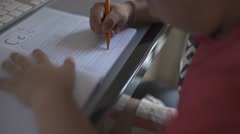 Closeup of kid practicing and learning to write letter C on an exercising book. Stock Footage