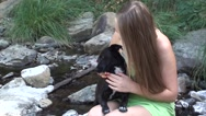 Pretty blonde girl sitting on the river with black dog Stock Footage