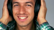 Close up of man smiles and listens to music on headphones Stock Footage