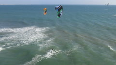 Kite surfers enjoying a windy day at the beach Stock Footage