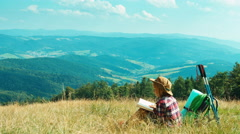 Portrait little hiker child girl 7-8 years reading book and sitting on mountains Stock Footage