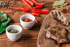 Two cooked steak with different condiment and knife on table. Stock Photos