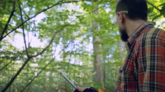 Forestry worker holding a tablet in woodland Stock Footage