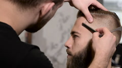 Professional hairdresser shaving man's chin with a straight razor in barbershop Stock Footage