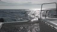 POV shot looking forward on catamaran as it cuts through waves under full sai Stock Footage