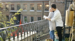 4K Happy young Asian couple in city apartment go onto balcony to look at view Stock Footage