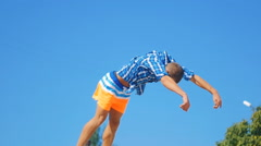 Guy athlete does an acrobatic front flip on the beach Stock Footage