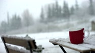 Red cup of coffee on a wooden table while snowing. Bistro. Stock Footage