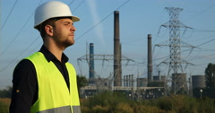 Pleased Engineer Man Looking in the Distance at Wire Lines Near Electric Tower Stock Footage