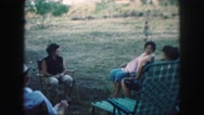 1958: adults sit in a circle outside while girl and boy play with yellow ball. Stock Footage