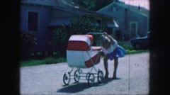 1958: cute baby girl playing dress up pushing baby buggy AMES, IOWA Stock Footage