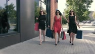 Three attractive young ladies are walking with their purchases Stock Footage