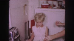 1958: a mother teaching her daughter how to cook eggs by the first time  Stock Footage