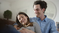 4K Cheerful couple expecting a baby relaxing together at home Stock Footage