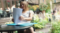 Sexy businesswoman working on papers in the outdoor cafe, steadycam shot Stock Footage