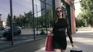 Wonderful woman is walking elegantly along the shop windows Stock Footage