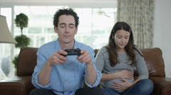 4K Competitive man playing video games at home, with bored pregnant wife Stock Footage
