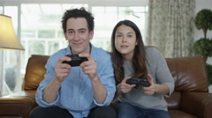 4K Competitive couple playing video games together at home Stock Footage