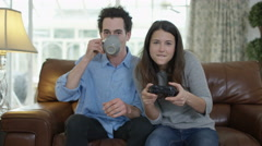 4K Competitive woman playing video games at home, with boyfriend beside her. Stock Footage