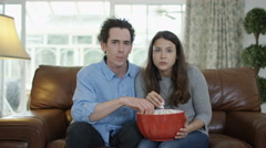 4K Couple watching TV & eating popcorn, shocked reaction the action on screen Stock Footage