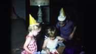 1958: two children anxiously watch the third open her birthday gift Stock Footage