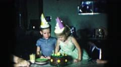 1958: adults and children gather at dining table around lit birthday cake  Stock Footage