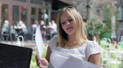 Busy businesswoman reading outcomes in the outdoor cafe and analyzes them Stock Footage