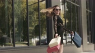 Happy young woman spins around with her shopping bags Stock Footage