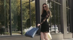 Young woman in black dress dancing on the street after successful shopping day Stock Footage