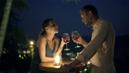 Young, beautiful couple talking and drinking wine in bar in the evening Stock Footage
