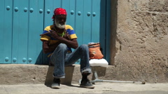 Elderly Afro-American man in red bandanna with cuban cigar sits on a step near Stock Footage