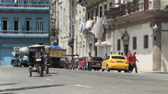 Two trishaws with passenger are riding on central road of touristic street in Stock Footage