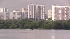 Water skier riding behind river boat on background of urban houses Stock Footage
