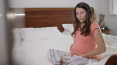 4K Pregnant woman in bedroom makes a phone call when the contractions begin Stock Footage