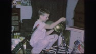 1958: a boy in white put on armor kept in the shelf and lady opens a box AMES Stock Footage