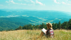 Portrait little hiker child girl 7-8 years reading book and sitting on grass Stock Footage