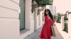Fair-skinned young lady in red dress walking elegantly down the street Stock Footage