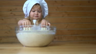 Cute baby in cook cap playing with dough Stock Footage