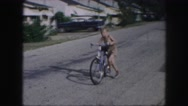 1958: a cute shirtless boy in shorts riding through the street on his bike  Stock Footage