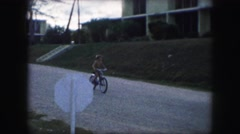 1958: a boy is riding his bike outside on the street. no shirt but seems happy. Stock Footage