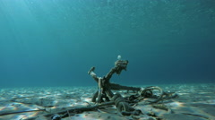 Fish passes by ship's old anchor and chain line under sea in Greece Stock Footage
