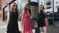 Three beautiful female friends walking along the shopping windows. Slow motion Stock Footage