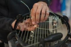 Close up of tennis stringer hands doing racket stringing Stock Photos