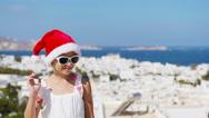 Little girl in santa hat outdoors background old street on Mykonos. Kid at Stock Footage