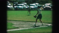 1958: boy pitching ball in green grass near parking lot AMES, IOWA Stock Footage