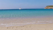 Word Enjoy handwritten on sandy beach with soft ocean wave on background. Idea Stock Footage